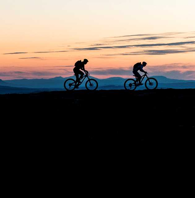 Two mountain bikers in silhouette in front of an evening sky
