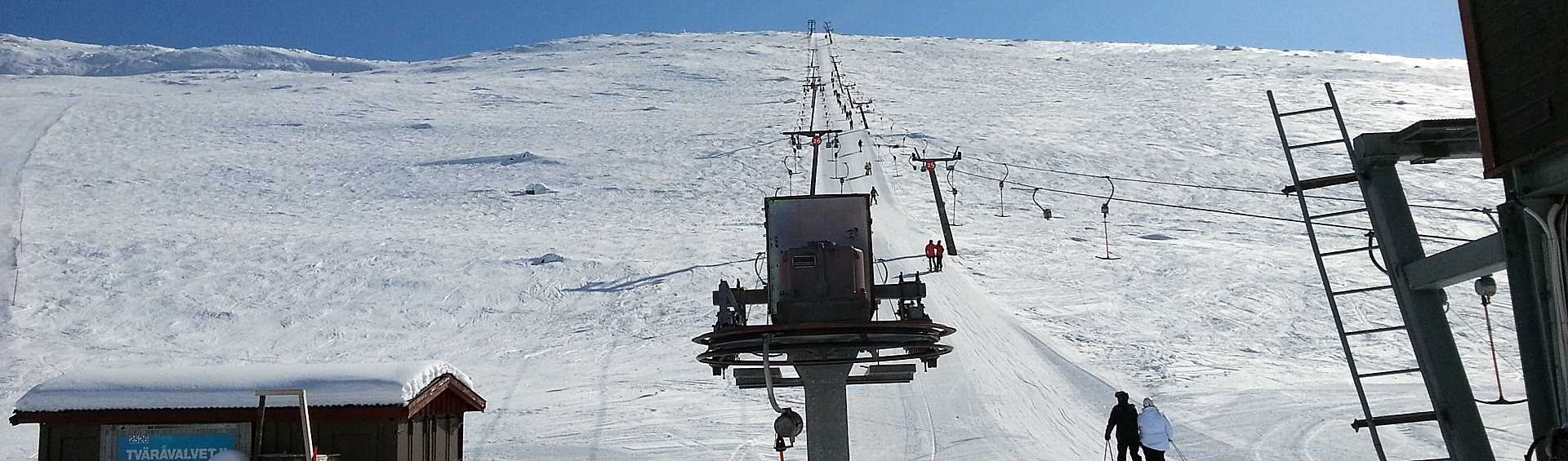 Skiers travelling in ski lift upwards a mountain slope