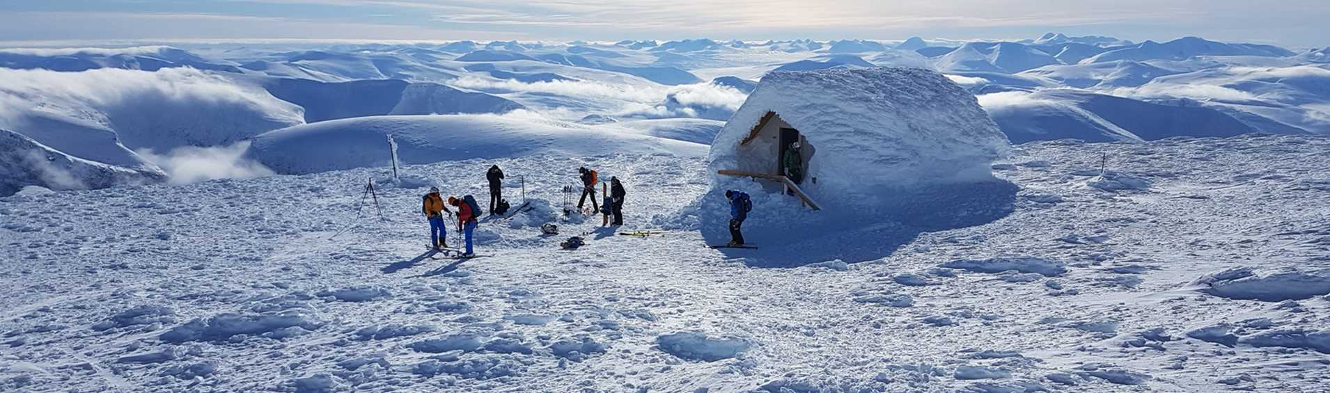 Skiers standing next to a cabin partly covered in snow