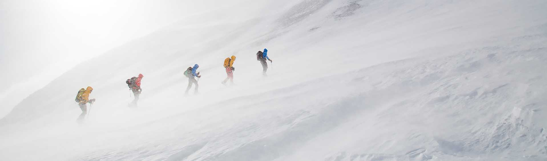 A group of cross country skiers travelling through a snowstorm